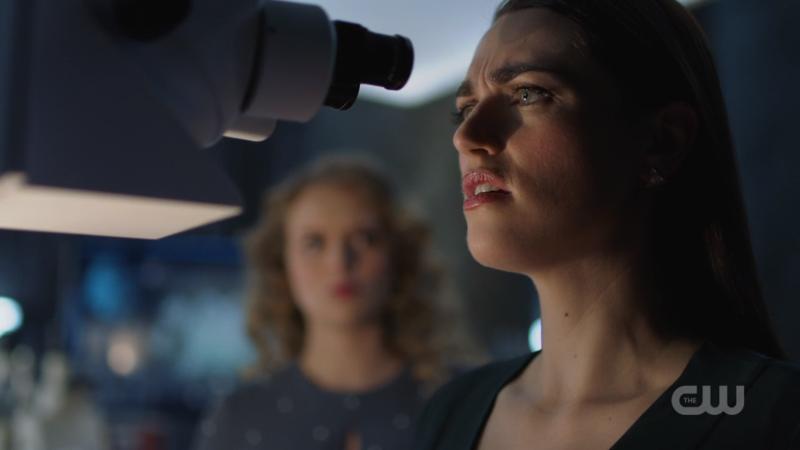 Lena looks through a microscope