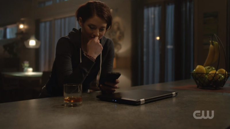 Alex puts down her whiskey and looks wistfully at her phone