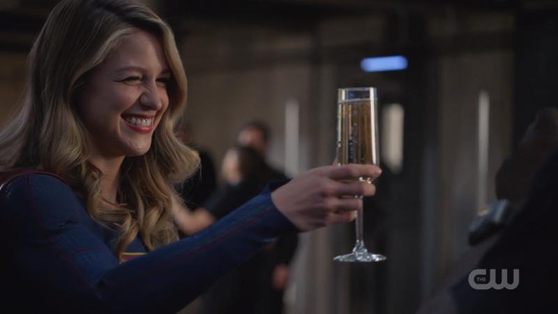 Kara raises a champagne glass