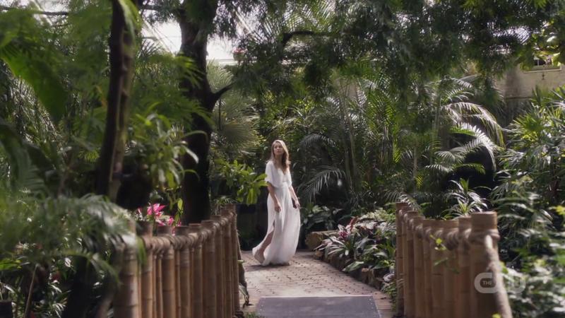 Kara is in a garden in a lovely white dress