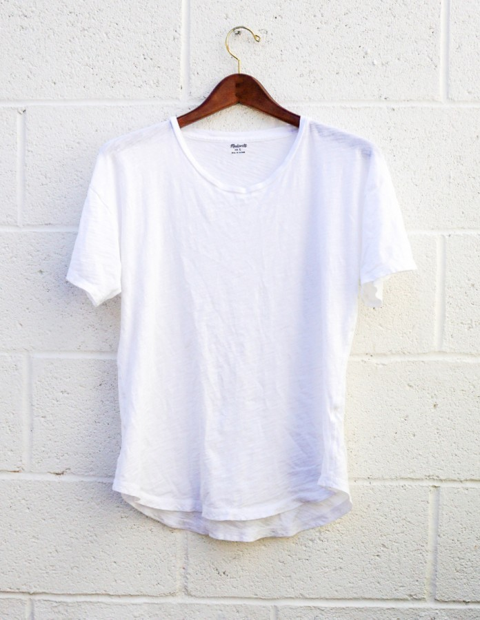 A white short-sleeved t-shirt, hanging against a white brick wall.