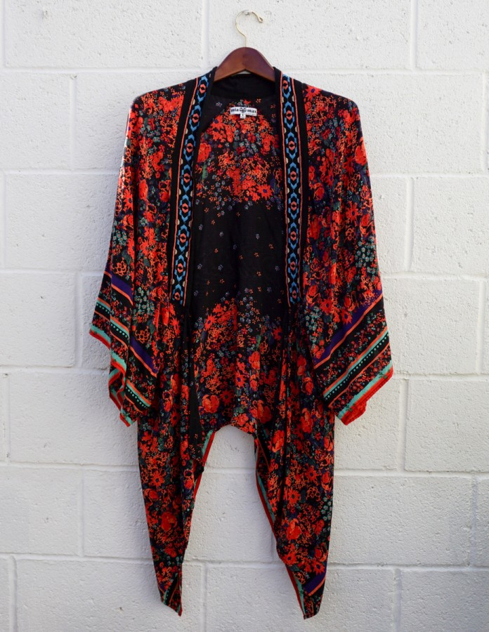 A black kimono-style robe with red floral print and decorative edging, hanging against a white brick wall.