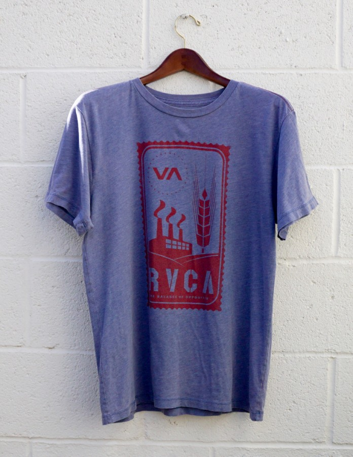A blue t-shirt with a red graphic design, with short sleeves, hanging against a white brick wall.