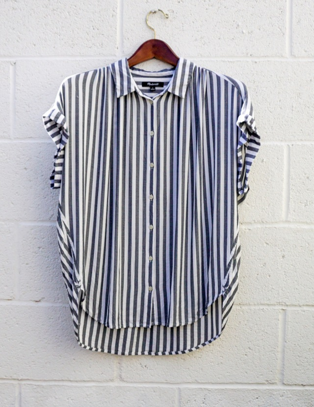 A blue and white striped shirt with short sleeves, hanging against a white brick wall.