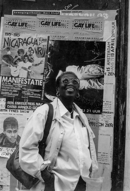 A black and white photo of Angela Bowen standing in front of a wall that's covered in posters and flyers, apparently for local art and queer community. She's wearing a white button down shirt, white jacket, large glasses, and a bag over her shoulder. She's smiling up toward the sky at something off-camera.