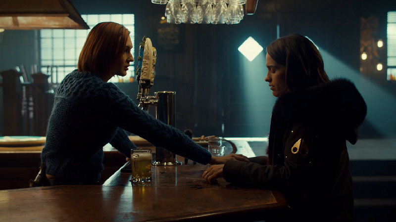 Nicole reaches over the bar to hold Wynonna's hand