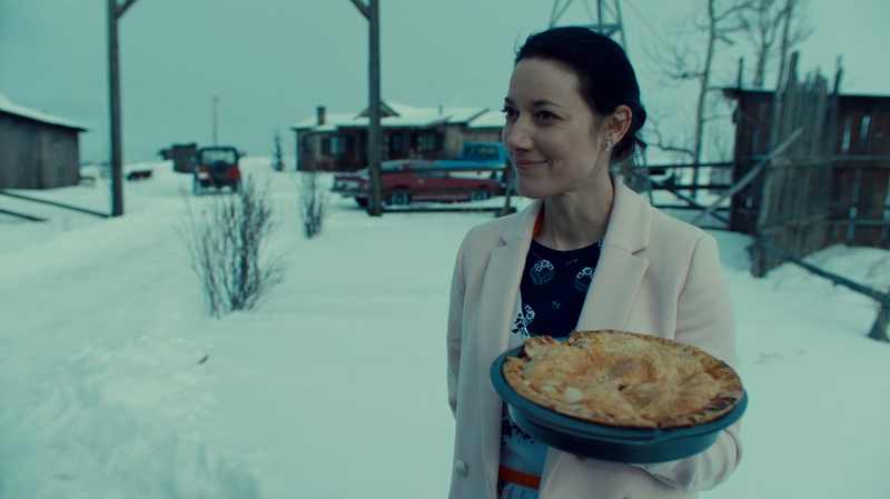 Jolene stands innocently holding a pie