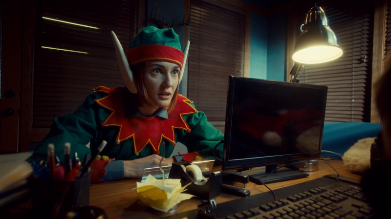 Nicole leans in seriously while wearing her elf costume