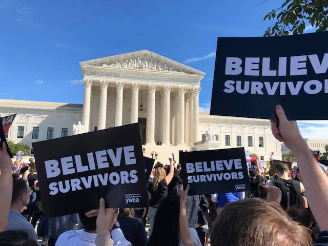 """Protestors gathered outside the U.S. Supreme Court, images of three black and white signs that say """"Believe Survivors"""" in the foreground with the Supreme Court in the background against a blue sky."""