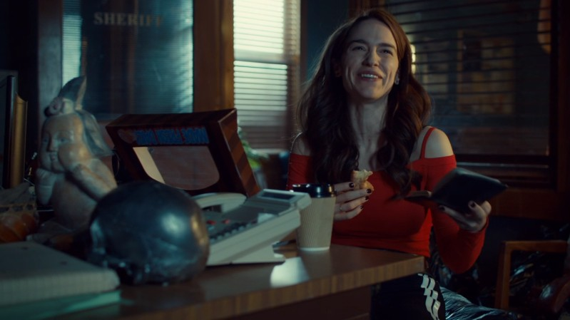 Wynonna eats a donut and cackles at her findings