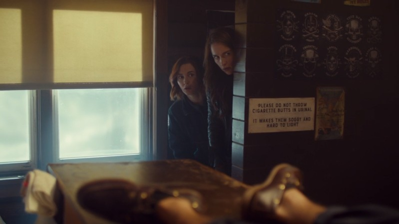Nicole and Wynonna peek their heads from around a wall