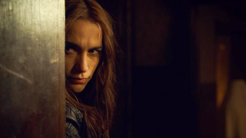 Wynonna peeps from behind a doorframe
