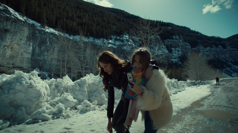Waverly holds the mitti n her mouth while trying to get service on her flip phone and holding up her sister