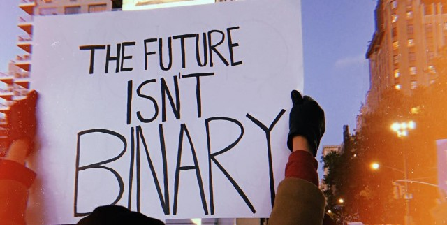 "A rally sign reads ""the future isn't binary"" in front of Washington Square."