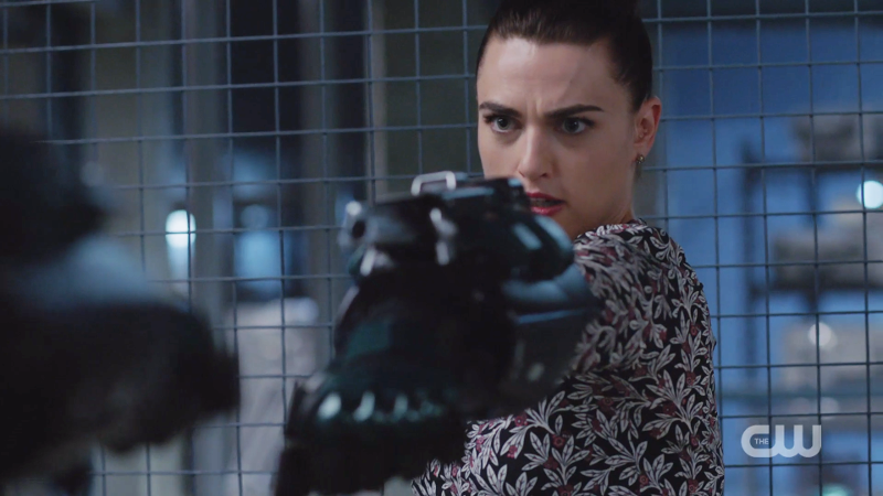 Lena holds up the suit's arm to shoot from it