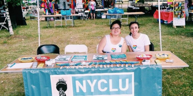 "Two people in rainbow heart t-shirts sit at a table with a banner across the front that reads, ""N-Y-C-L-U: New York Civil Liberties Union"" and literature, fans, and pins at a Pride event with more tables and people in the background."