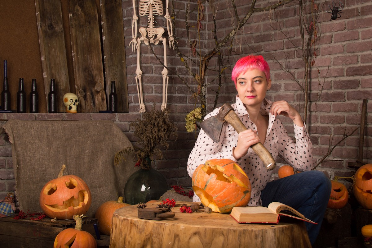 A pink-haired femme-ish woman holding an axe, surrounded by pumpkins, and looking off into the middle distance, with a book on the treestump in front of her for some reason (she is also inside)