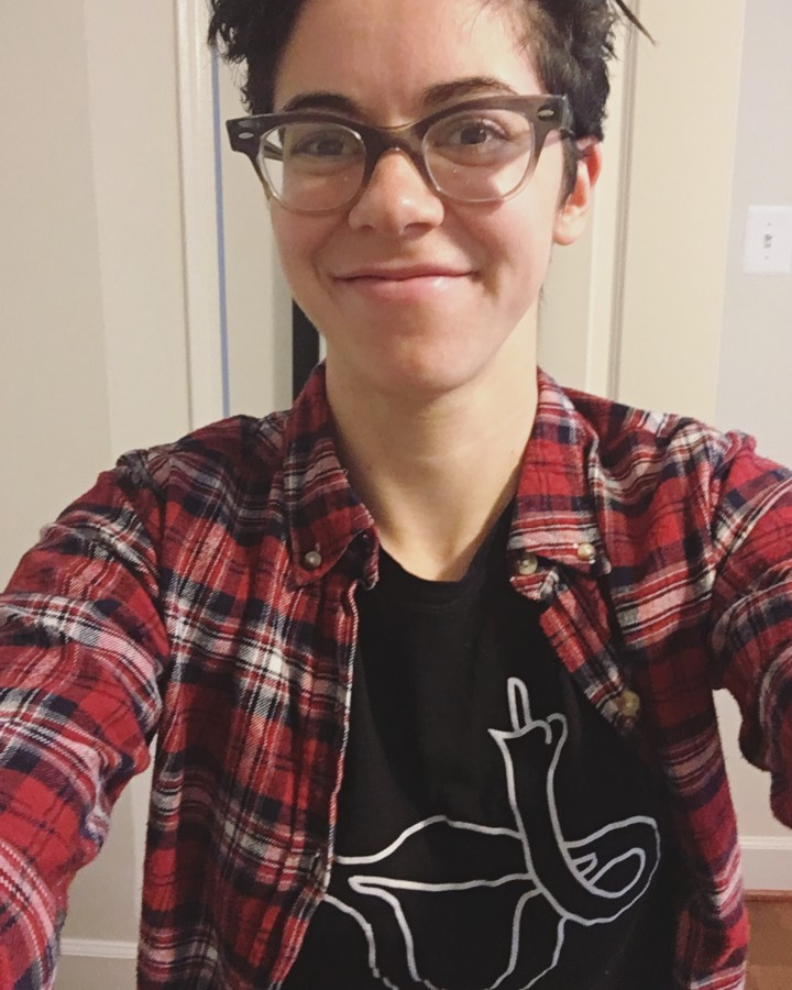 Carrie wearing a red flannel over a shirt with a cartoon uterus giving the middle finger.