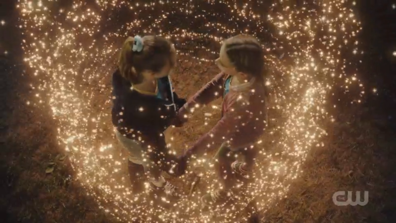 Little Ava and Little Sara hold hands amidst the sparkles