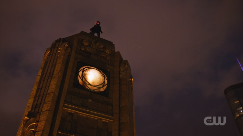 batwoman stands on a rooftop