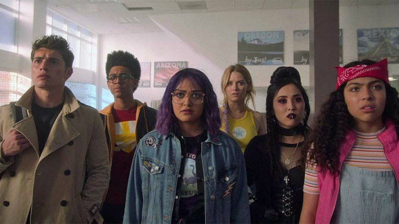 Image: The Runaways crew staring at something that confuses them. Gertie is front and center with purple hair and a jean jacket, and Karolina and Nico (the girl-girl couple) are to her left, as well as her sister. The two boys are to her right.
