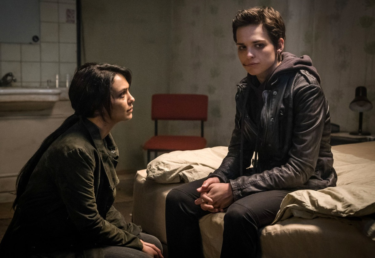 Image: Baldwin, a masculine-of-center woman in a hoodie, black leather jacket and black pants, is sitting on a bed in a room. She has short hair and her face is bruised. Clare, a white woman with long dark hair in a ponytail, is sitting on the ground, looking at Baldwin, who is looking away. They seem sad and alarmed.