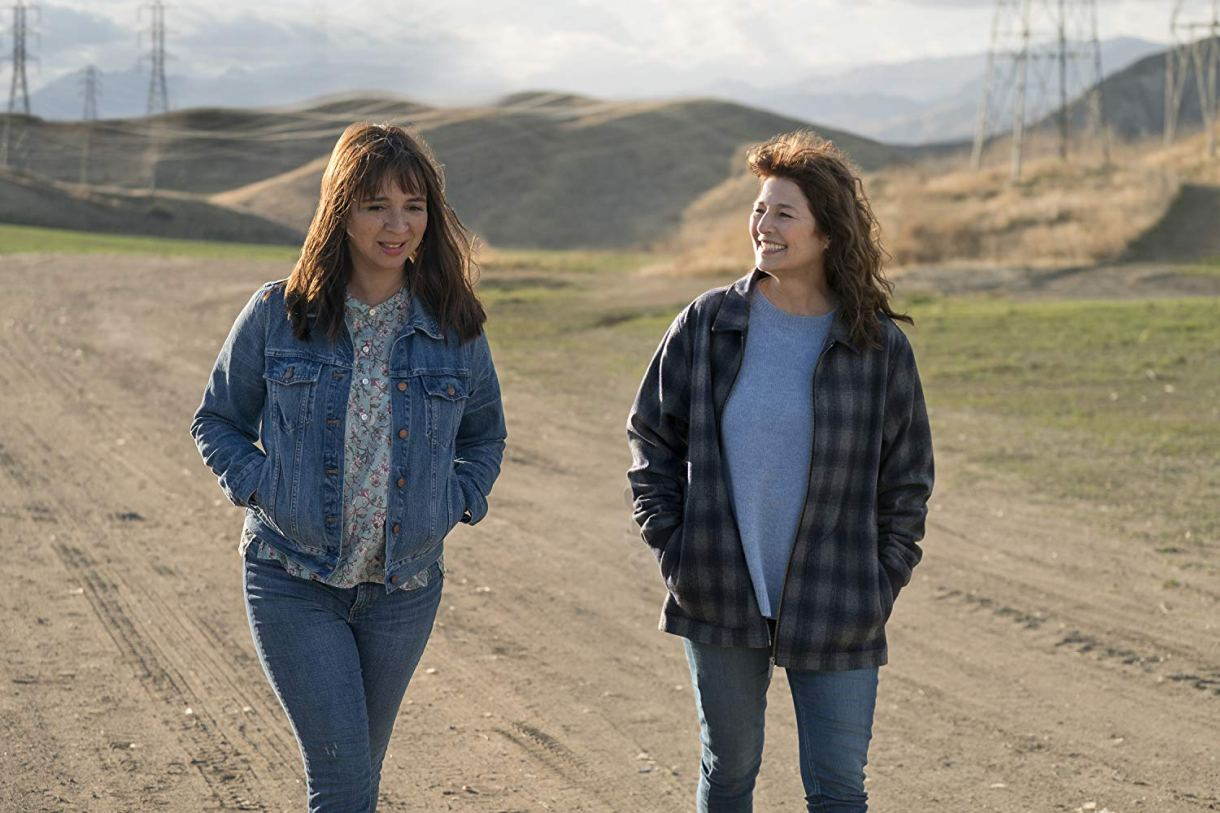 Image: Two women walk a dusty road. One is June, played by Maya Rudolph, and the other is Kase, played by Catherine Keener. Case is wearing a big lesbian flannel and smiling at June, who's wearing a denim jacket.