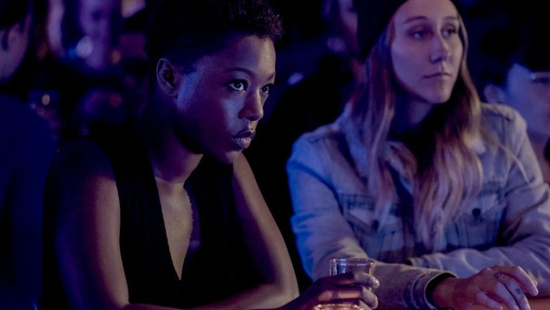 Image: Moira (Samira Wiley) is sitting at a darkened bar, looking intense.