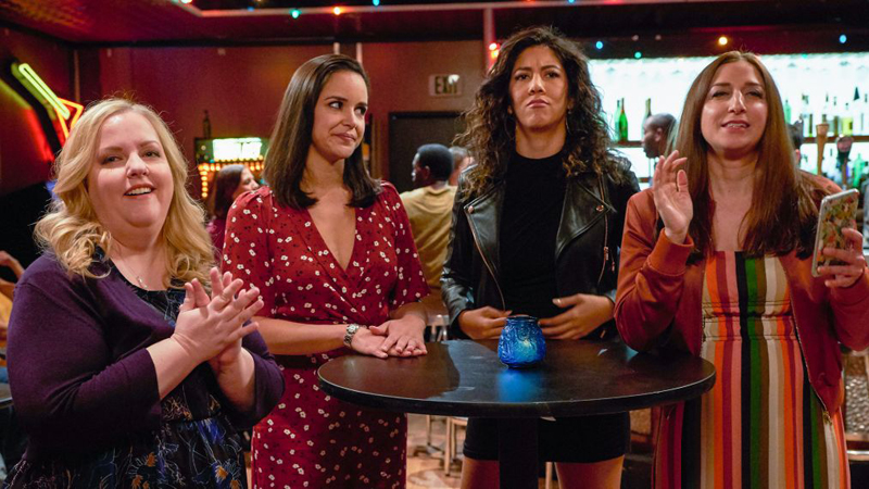 Image: four women at a bar, one of them is Stephanie Beatriz in a leather jacket