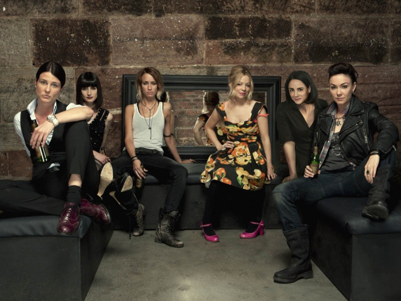 image: the cast of lip service sitting on a U-shaped bench in a basement with a mirror on the wall.