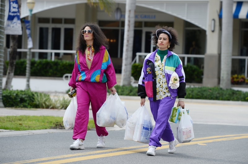 Image: Abby and Ilana are wearing brightly colored tracksuits and carring stuffed plastic bags of groceries. Their hair is frizzy because of Floria humidity.
