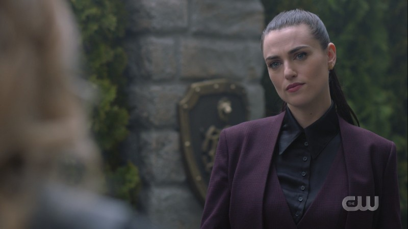 Lena smirks in the garden in her suit