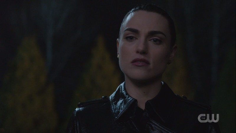 Lena looks stern in a waterproof leather-looking rain trenchcoat??
