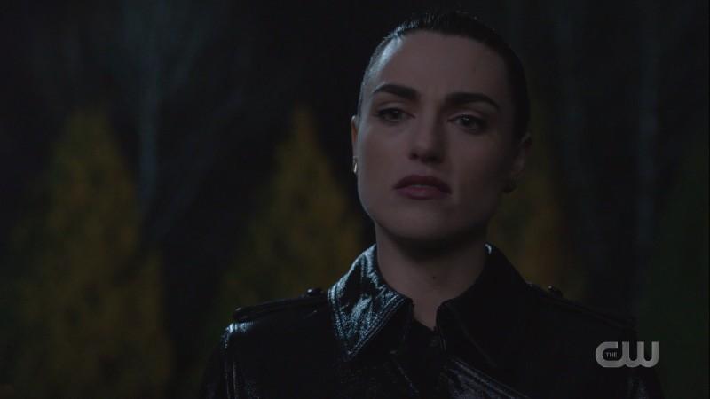 Lena looks stern in a waterproof leather-looking rain trenchcoat??