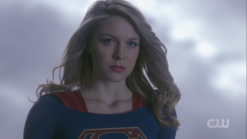 Supergirl flies up next to the helicopter