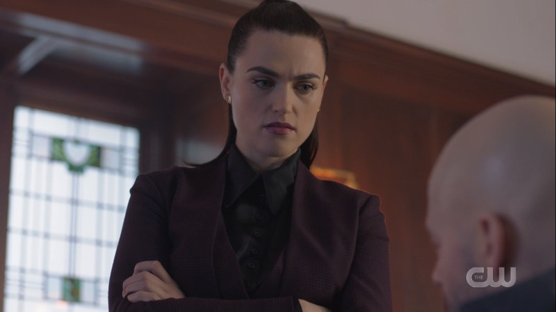 Lena crosses her arms in a suit