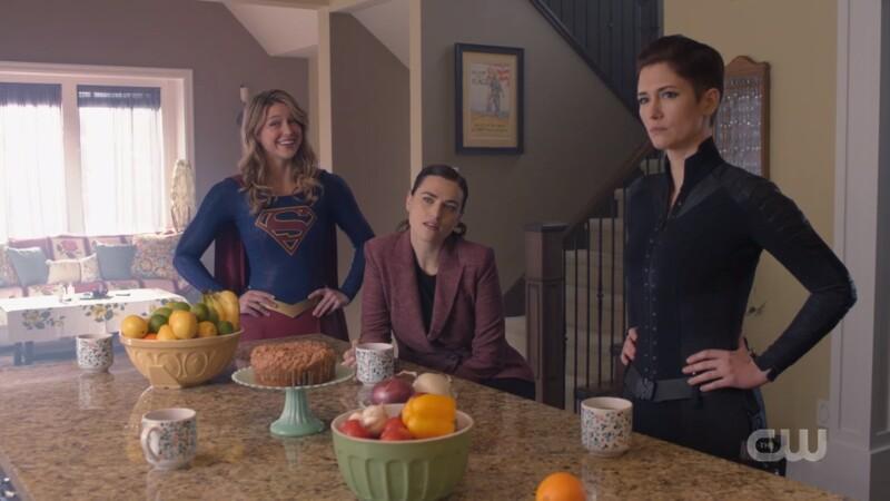 Supergirl looks cheerful, Lena looks untrusting, Alex looks stern