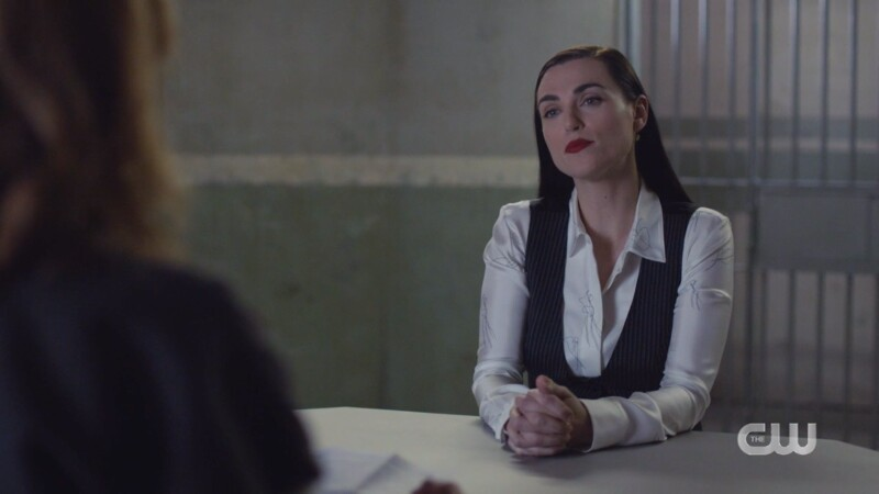 Lena is in a white silky blouse and a black pinstripe vest and her hair is down but kind of slicked back