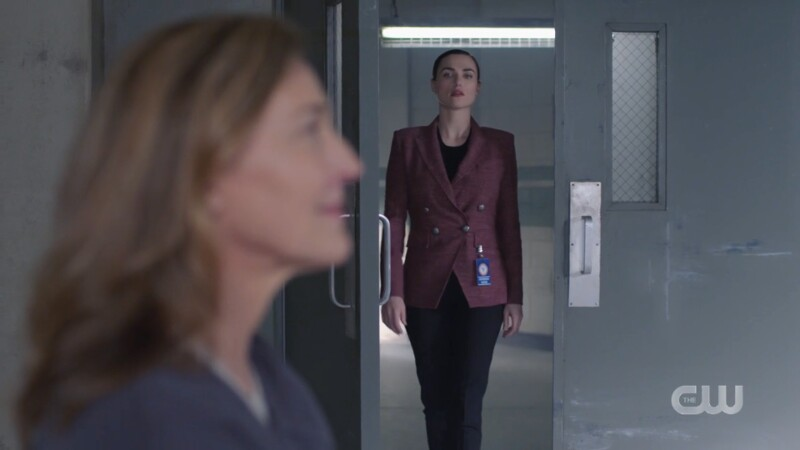 Lena struts into the room wearing a tweed-ish but cute purple blazer and black pants