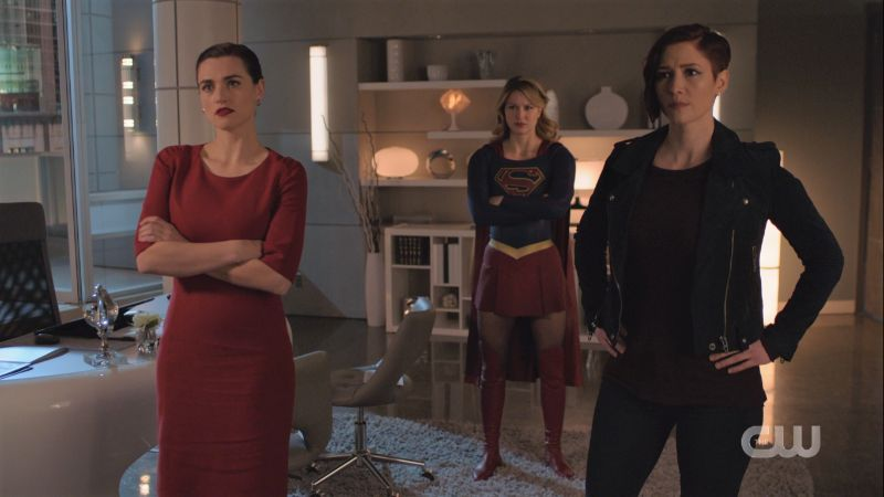 Lena Supergirl and Alex sand around with crossed arms or hands on hips staring angrily at the TV