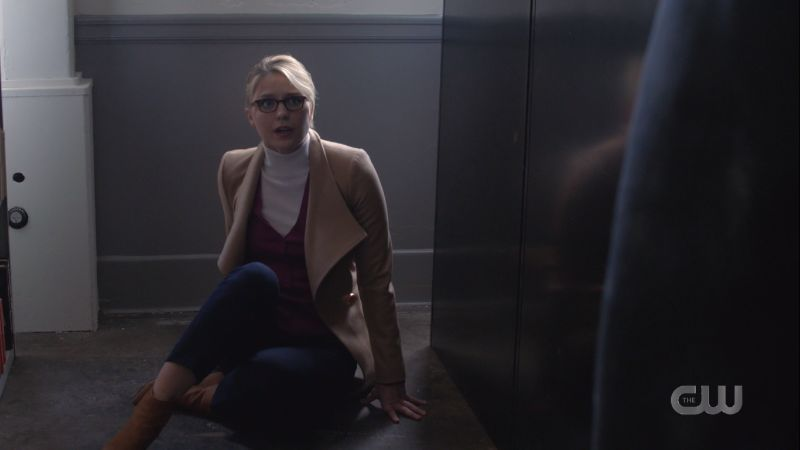 Kara scurries backwards on the floor faking fear