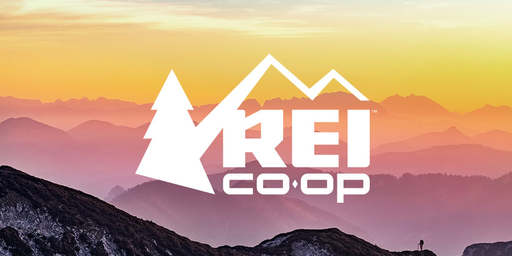 rei logo overlaid on a background with a sunset sinking below a mountainous landscape