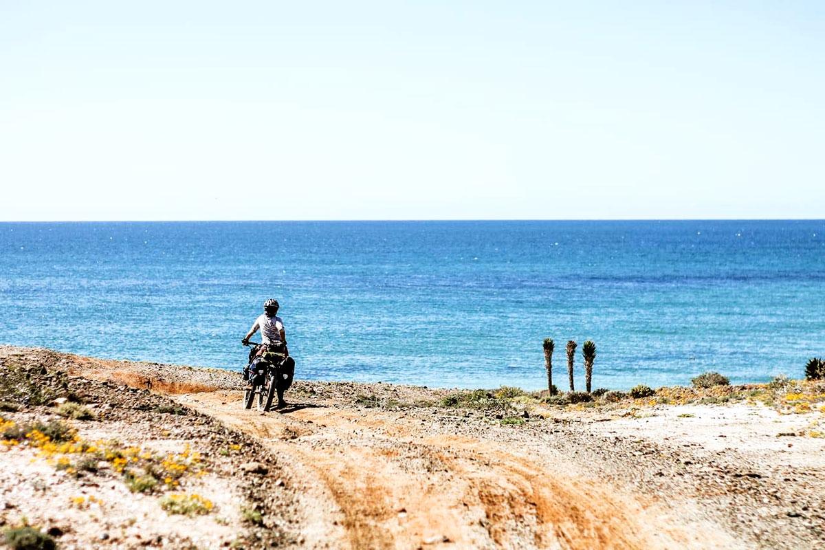 author on bike in front of ocean