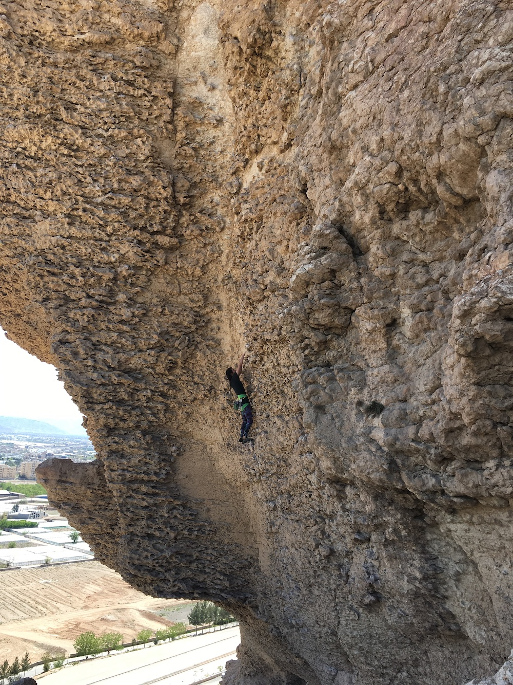 photo of the author climbing up a sheer rock face with a city in the background