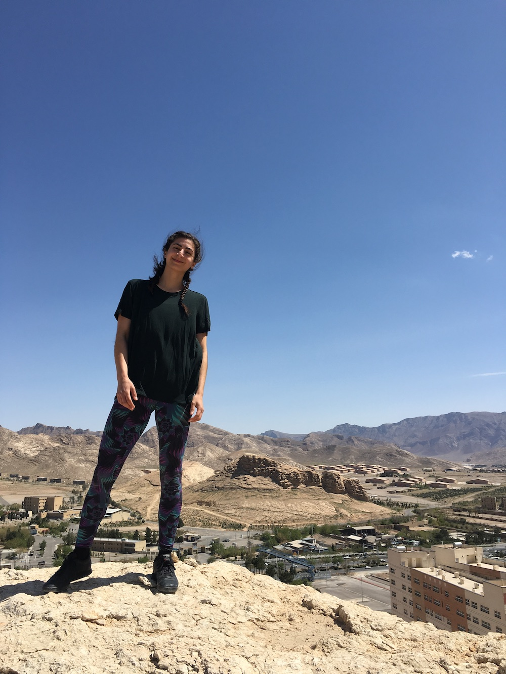 Portrait of the author standing on a rock outcropping with a city behind her