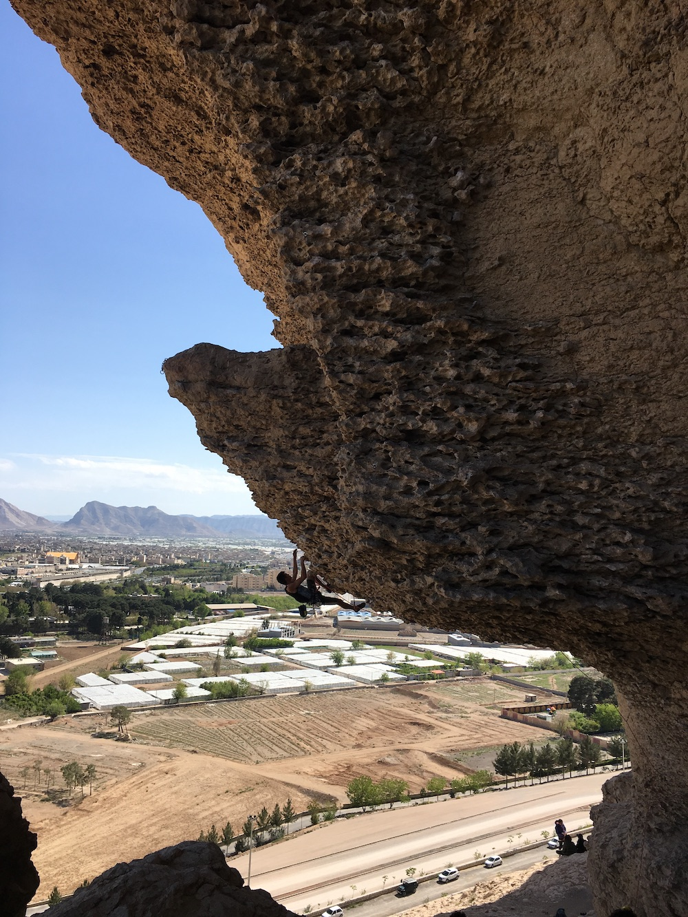 photo of someone climbing up a rock face, suspended on the underside of an outcropping