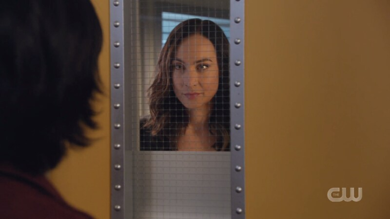 Nora glares evilly through the widow of the door