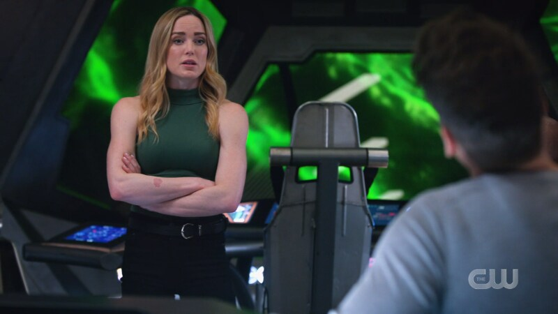 Sara stands with her arms crossed looking buff as hell