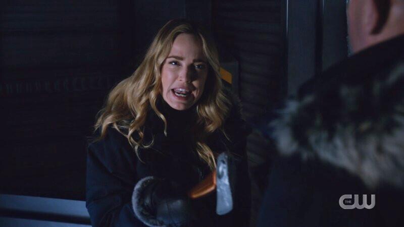 Sara yells at Mick while pointing the hatchet at him