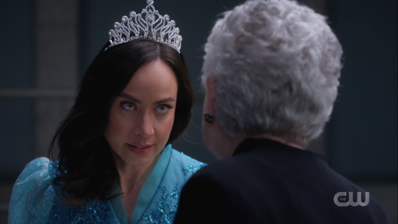 Nora is wearing a tiara and a puffy blue dress but also she's glowering